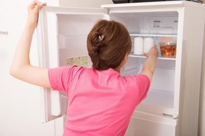 冷蔵庫の中から缶を取り出そうとしている女性